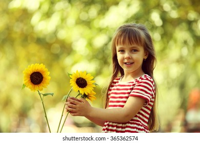 Little girl with sunflowers in the park