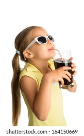 Little girl in sunglasses drinking cola beverage through a straw and looking at something above her, smiling