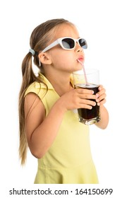 Little girl in sunglasses drinking cola beverage through a straw and looking at something above her