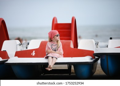 Little girl in sunglasses and kerchief sitting on the beach. Sad blond girl in fathers t-shirt dreaming about something on the pedal boat. Lido di Jesolo, Italy. Summer vacation with children concept.
