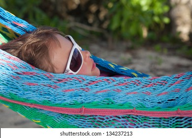 Little girl with sunglasses on a hammock