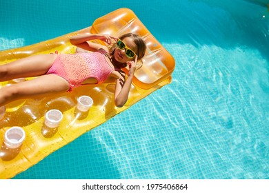 Little girl in sunglasses relaxing in swimming pool, enjoying suntans, swims on inflatable yellow mattress and has fun in water on family vacation, tropical holiday resort, view from above, copy space