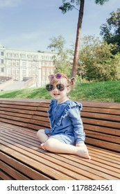 Little girl in sunglasses sitting on the bench in a city park on a warm sunny day