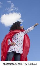 little girl superhero against blue sky
