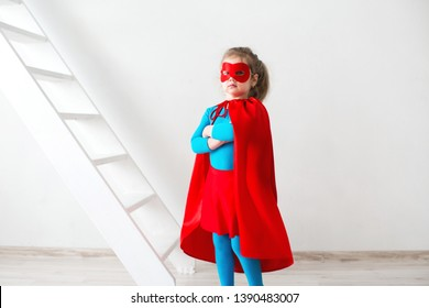 Little girl superhero in a red cloak and mask on white background. Concept of victory and success.