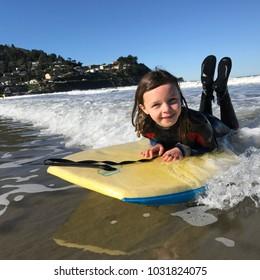 Little Girl surfing in California