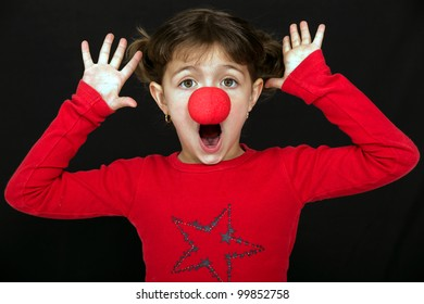 Little girl surprised with a clown nose