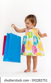 Little girl is surprised with colorful paper bags isolated on white background.