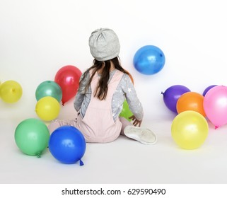 Little girl surrounded by balloons