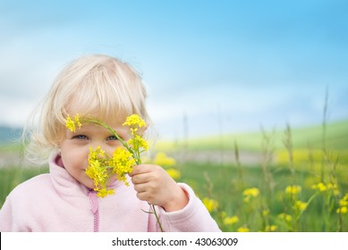Little girl swelling yellow flowers in the field.