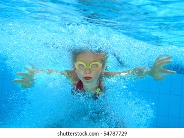 Little girl swim underwater in pool.