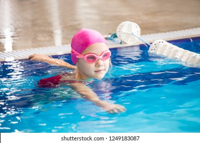 little  girl swimming in blue  pool