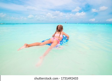 Little girl swimming on a surfboard in the turquoise sea