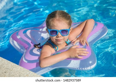 A little girl is swimming in the outdoor pool. The child is floats in an inflatable circle and sunglasses.