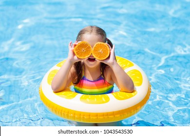 Little girl in swimming pool with inflatable toy ring eating orange. Kids swim on summer vacation. Tropical fruit and healthy snack. Swim aids for child.  Kid on colorful float. Beach and water fun