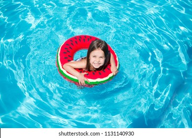 Little girl swimming in the pool with rubber ring, having fun in swimming pool.