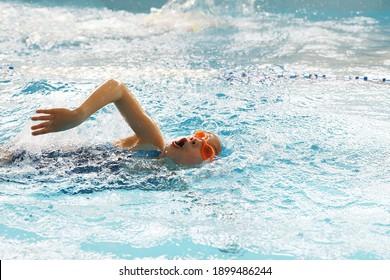 kleines Mädchen, das im Schwimmbecken schwimmt