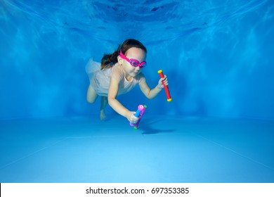 Little girl swims underwater and picking up toys from the bottom of the pool on a blue background. Portrait. The view from under the water. Landscape orientation