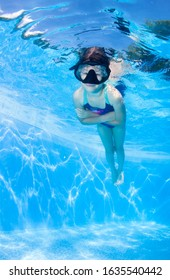 Little girl swims underwater in the pool .