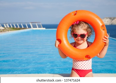 little girl in swimsuit takes lifebuoys background swimming pool