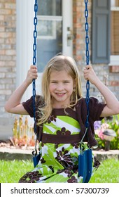 Little Girl Swinging in Front of Her House