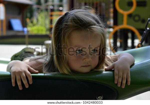 Little girl swinging lying on a swing
