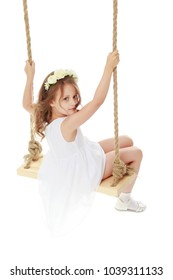 A little girl is swinging on a rope swing. The concept of a happy childhood, summer holidays, playing in a playground or in a kindergarten. Isolated on white background.