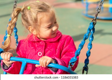 little girl swinging on a swing in red clothes
