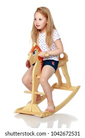 Little girl swinging on a wooden horse. The concept of a happy childhood, games in kindergarten and in the family. Isolated against white background.
