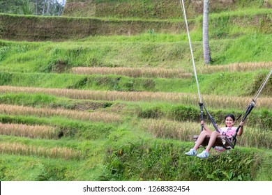 Little Girl Swinging Over the Tegalalang Rice Fields in Ubud, Bali, Indonesia
