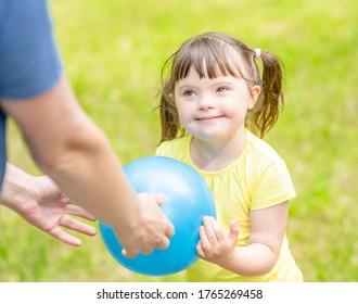 Kleines Mädchen mit Syndrom unten und ihre Mutter spielen mit einem Ball im Sommerpark