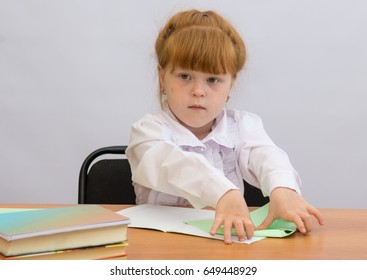 The little girl at the table holding a Paper Airplane