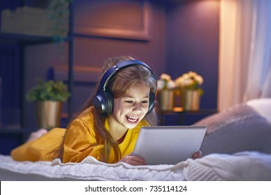Little girl with tablet and headphones on the bed at home. Child girl listening to music.