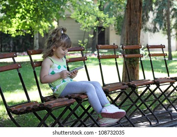 little girl with tablet sitting in park