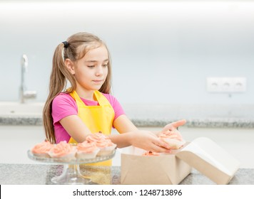 little girl takes out the capcake from the gift box at kitchen