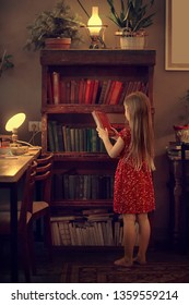 Little girl is taking a book from bookshelves. Image with selective focus and toning.