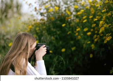 Little girl taking a picture of the flowers