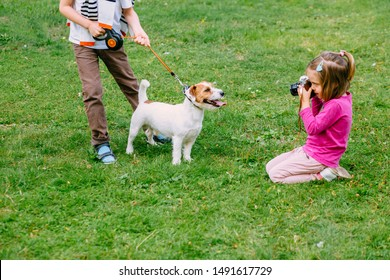 Little girl taking picture using vintage film camera. Cute little kid photographing her older brother with dog Jack Russell terrier posing on grass outdoor in park. Pet, love, friendship concept.