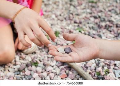 Kleines Mädchen, das Steine aus der Hand von Freunden holt. Vertrauensbegriff