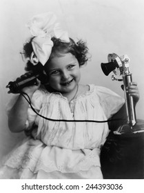 Little girl talking on an early model telephone. Ca. 1905.