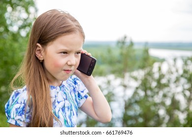 Little girl talking on the phone outdoors