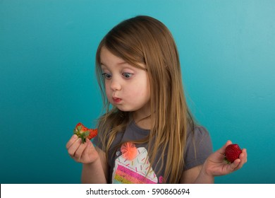 Little girl tasting a strawberry