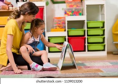 Little girl and teacher reading book