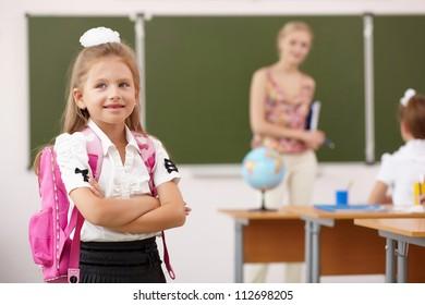 Little girl with a teacher studying at school class