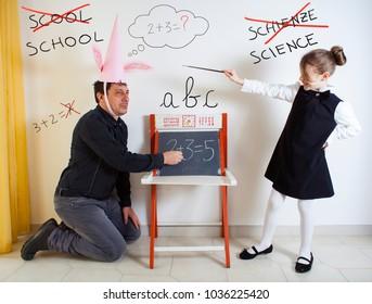Little girl teaching mathematics to an adult dunce on little chalkboard