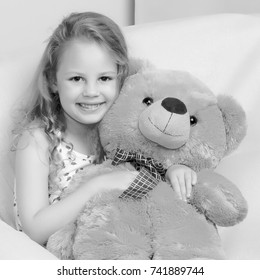 Little girl with a teddy bear. The concept of the game, raising a child in kindergarten and in the family.