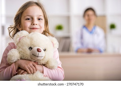 Little girl with teddy bear is looking at the camera. Female doctor on background.