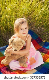 Little girl with teddy bear on nature