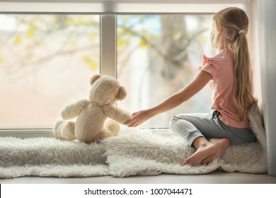 Little girl with teddy bear sitting on window sill. Autism concept