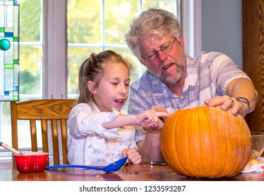A little girl tells grandpa exactly where she wants a pumpkin face carved
